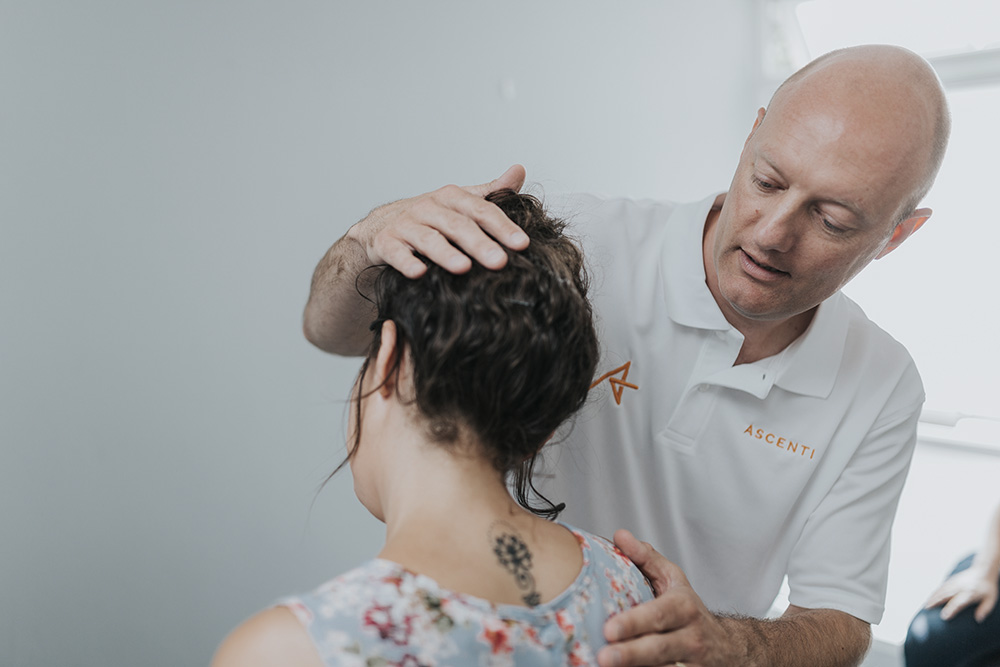 Ascenti physio administering treatment for a neck complaint